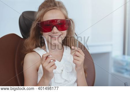 Dental Treatment Concept. Lovely Happy Little Girl Wearing Protective Uv Glasses, Sitting In A Denta