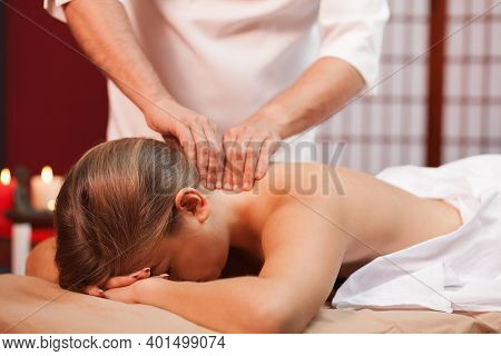 Professional Spa Masseur Massaging Neck Of A Female Client. Woman Relaxing During Full Body Soothing