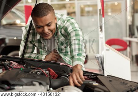Male Customer Checking Out Engine Of A New Car For Sale. Attractive Cheerful Man Examining Motor Of