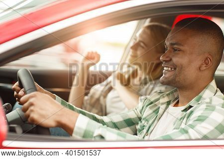 Happy Couple Travelling By Car Together. Handsome African Man Smiling Joyfully While Driving His Car