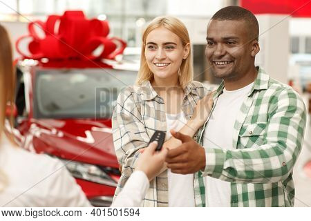 Young Loving Couple Hugging While Receiving Keys To Their New Automobile From Car Seller. Handsome A