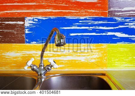 Plumbing And Sewerage - Kitchen Water Tap Faucet On A Motley Background