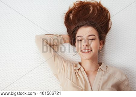 Close Up Of A Happy Woman Enjoying Lying On Comfortable Orthopedic Mattress, Copy Space