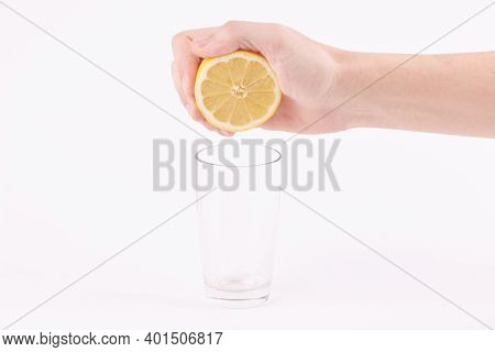 Caucasian Person Squeeze Lemon Juice In A Glass On A Grey Background.