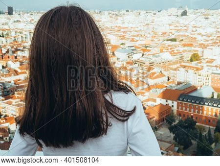 The Picture Shows A Back View Of A Little Girl Looking At The Skyline Of The City Of Madrid On A Sun