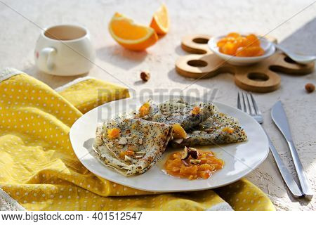 Thin Crepe Pancakes With Poppy Seeds, Orange Jam And Chopped Hazelnuts On A White Plate On A Light C