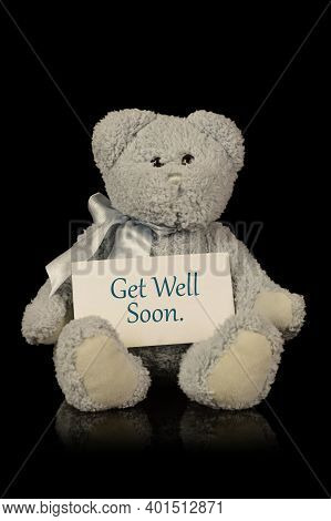 An Isolated Over Black Image Of A Teddy Bear With A Get Well Soon Message Of Compassion.