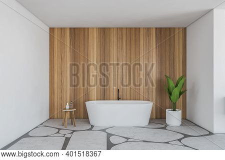 White And Wooden Bathroom With Bathtub And Table With Plant. Bathtub Against Wooden Wall On Light Gr