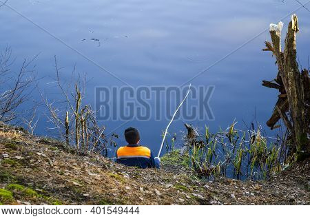 Angler With A Fishing Rod In His Hands On The Lake
