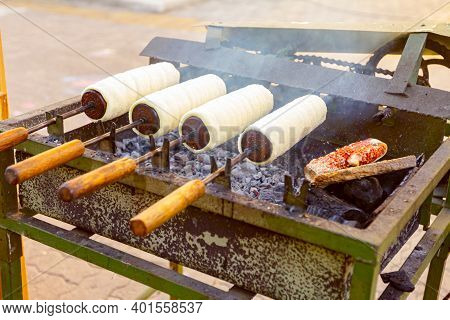 Traditional Hungarian Spit Cinnamon, Chimney Cake Is Rotate For Equal Baking Over Glowing Charcoal E
