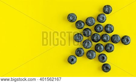 Fresh Organic Blueberries On Yellow Background In A Shape Of Star With Copy Space. View From Above,