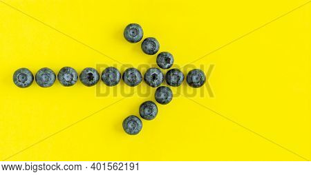 Fresh Organic Blueberries Arranged In A Shape Of An Arrow On Yellow Background. View From Above, Fla