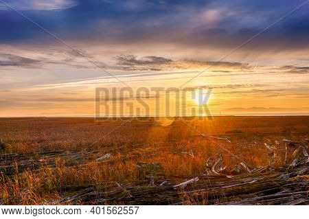 Beautiful Hdr Sunset Landscape. The Setting Sun Creates Sun Rays In The Clouds. Lens Flare Is Visibl