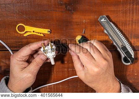 Installation Of Wires In A Plug. The Electrician Connects The Plug To The Electrical Wires. Close-up