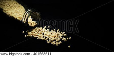 Closeup Of Urad Dal (white) In A Glass Container Spilled On A Isolated Black Background With Copy Sp