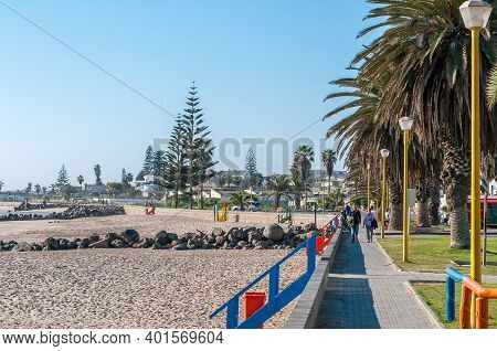 Swakopmund, Namibia - June 18, 2012: A Beach Scene At The Waterfront In Swakopmund. Palm Trees And P