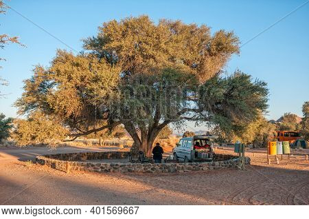 Sesriem, Namibia - June 22, 2012: A Camping Site Under A Large Camel-thorn Tree At Sesriem. One Pers