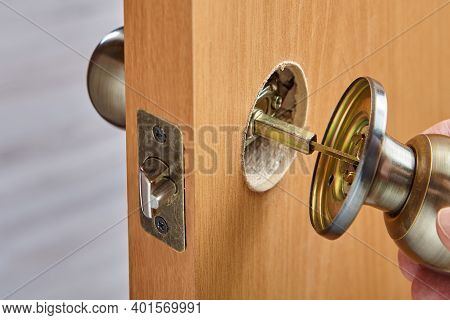 A Handyman Connects The Two Pieces Of A Door Knob With A Spindle While Assembling The Handle With A