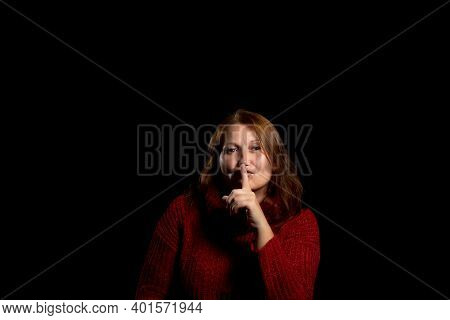 Pretty Woman In A Red Woolen Sweater With Her Index Finger In Her Mouth Commanding Silence On A Blac