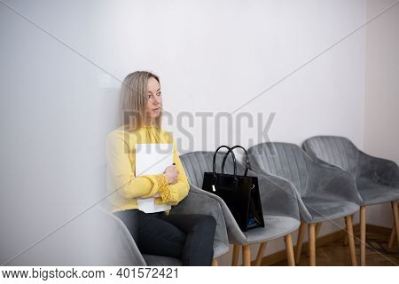 Blond Woman In A Yellow Blouse Waiting For A Job Interview In An Office Waiting Room.