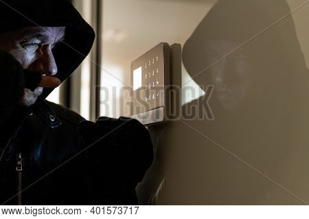 Burglary Into The Apartment At Night. The Thief Tries To Disarm The Alarm.