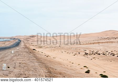 A View Of Road B2 Between Swakopmund And Walvis Bay. Vehicles And Sand Dunes Are Visible