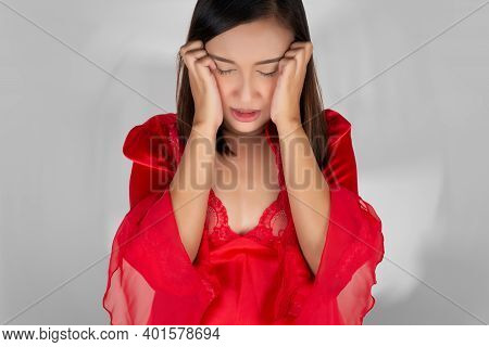 A Woman In A Red Satin Nightgown Woke Up From A Nightmare. On A Gray Background. Female With Poor Me