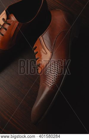 Mens Brown Shoes Standing On The Wooden Floor Background