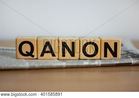 Q Anon Symbol. Cubes Placed On A Newspaper With The Word 'qanon'. Beautiful Wooden Table. White Back