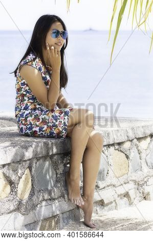 Young Attractive Girl Sitting On A Stone Wall