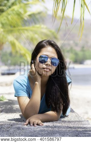 Young Indonesian Girl With Sunglasses Lying On A Stone Wall