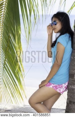 Young Indonesian Girl With Sunglasses Standing Under A Palm Tree