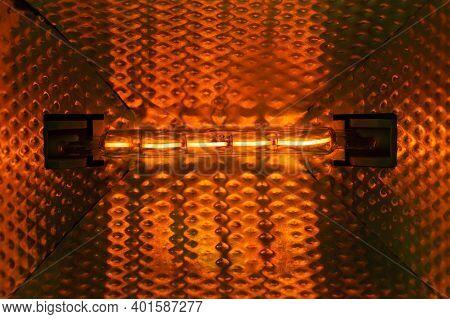 Filament Halogen Floodlight. Warm Orange Light. Weak Filament Glow. Glowing Lamp.