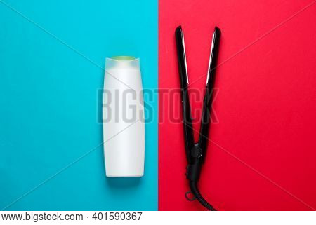 Set Of Products And Devices For Hair Care. Hair Straightener With A Bottle Of Shampoo On A Blue Red