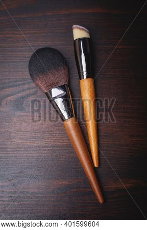 Makeup Brushes On A Brown Wooden Background