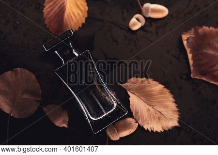 Perfume And Autumn Leaves On A Dark Background