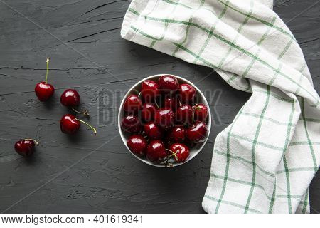 Fresh Cherries On White Bowl And Kitchen Towel On Concrete Black Background, Top View.