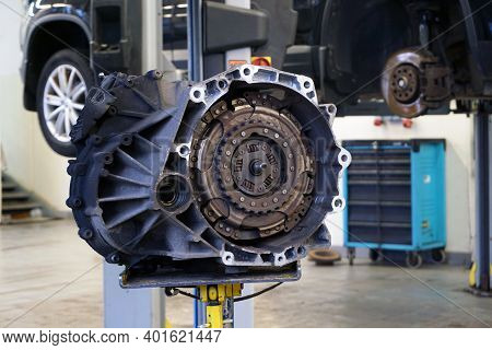 Automatic Transmission (dsg) Removed From Vehicle For Repair. In The Background, The Interior Of A C