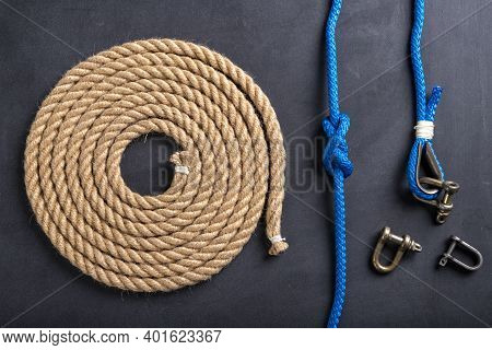 Rope Coiled Into A Circle, Knots And Shackles. Accessories For Sea Wolves On The Table.