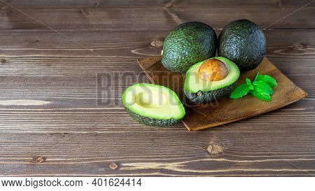 Group Of Fresh Ripe Whole And Halved Avocados On The Wooden Table. Healthy Vegetarian Eating. Banner