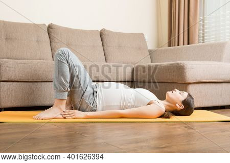 Beautiful Young Pregnant Woman Sitting Near Sofa In Yoga Pose At The Home. Pregnancy Yoga And Fitnes