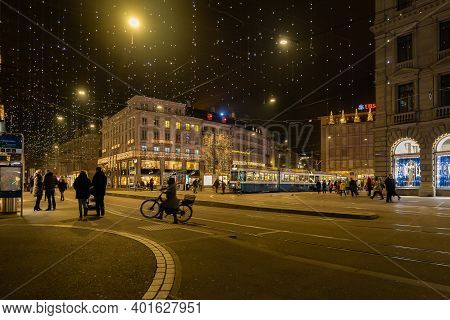 Traffic At Illuminated Paradeplatz At Christmastime At Night. Pedestrian And Cyclist Walking Near Tr
