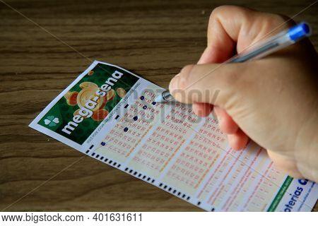 Salvador, Bahia, Brazil - January 2, 2021: Person Scoring Mega Sena Lottery Ticket In The City Of Sa