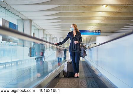 Young Elegant Business Woman Wearing Protective Face Mask With Hand Luggage On Travelator On Interna