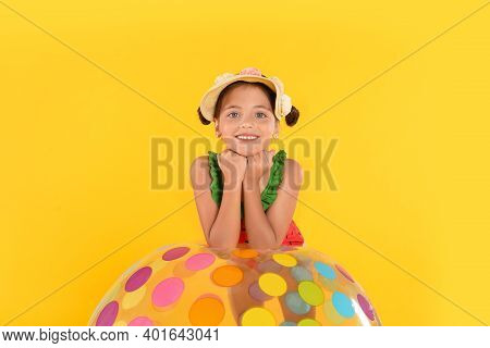 Cute Little Child In Beachwear With Bright Inflatable Ball On Yellow Background