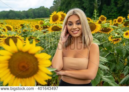 A gorgeous young blonde model poses outdoors in a field of sunflowers while enjoying a summers day