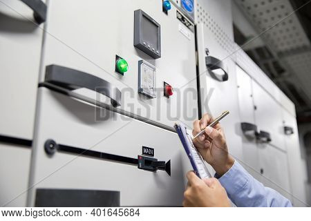 Electrical Engineer Checking Electric Current Voltage At Circuit Breaker Of Air Handling Unit (ahu)