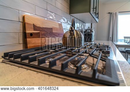 Cooktop With Kettle Over Burner And Cast Iron Grate Inside A Residential Kitchen