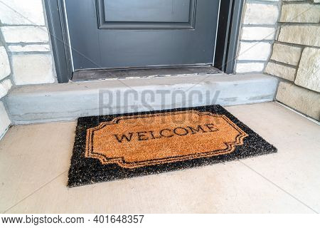Welcome Doormat Placed In Front Of The Gray Front Door Of A Home Entrance