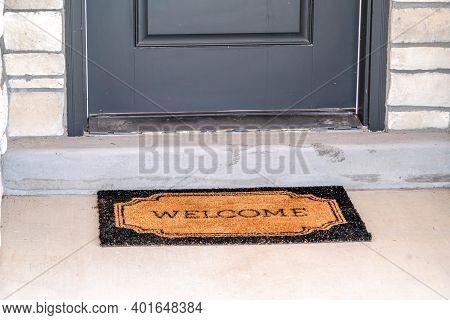 Doormat In Front Of Doorstep And Gray Front Door Of Home With White Stone Wall